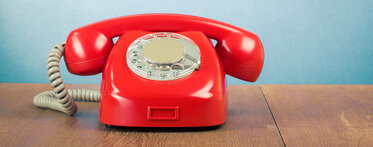 Photo of an old red telephone on a desk